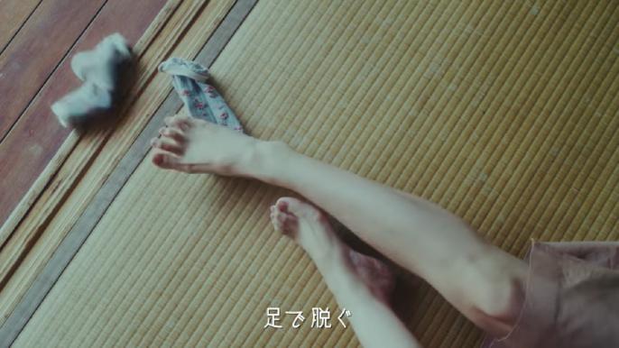 足で靴下を脱ぐ