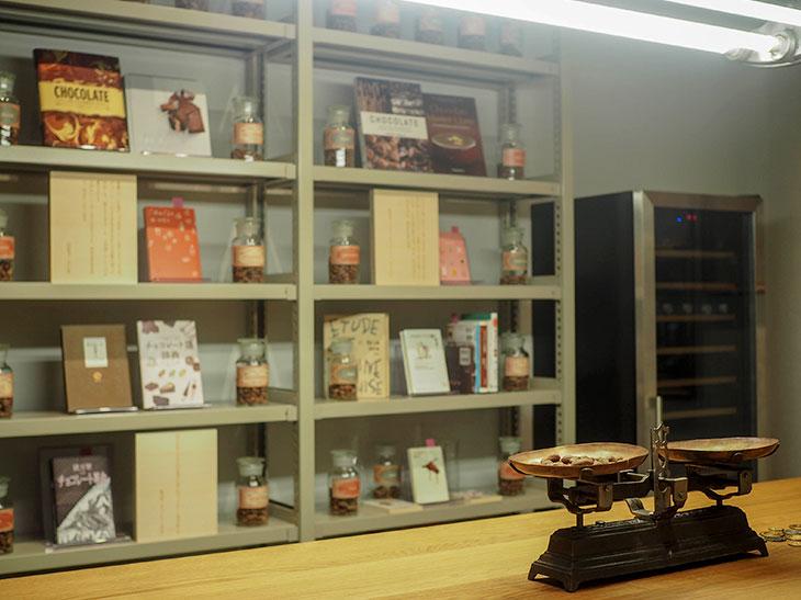 室内のテーブル上のカカオ豆がのった天秤は、中南米ではカカオ豆を貨幣として使用していた歴史があることになぞらえてのもの