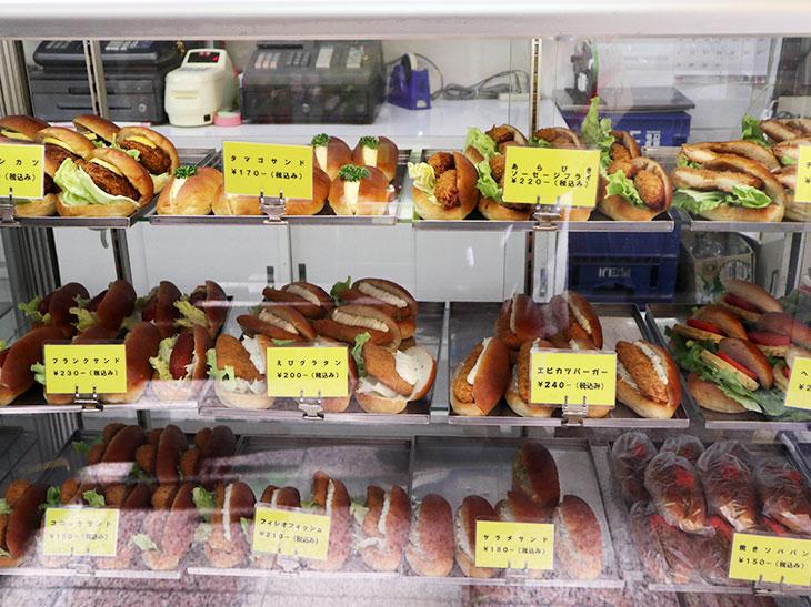 右のガラスケースには20種類以上の「おかずパン」、左にはクリームパンやアンパンなどの「おやつパン」がずらりと並ぶ