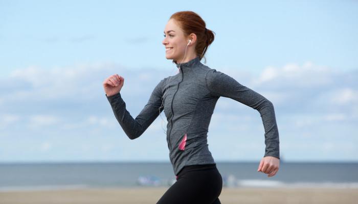 海辺にて笑顔でウォーキングをする女性