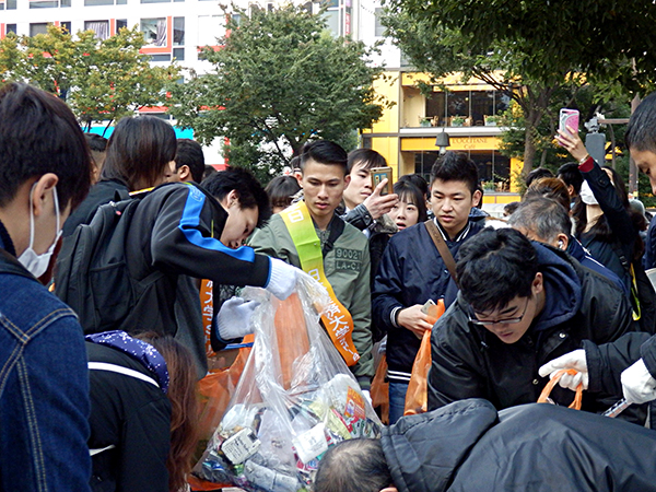 早朝から地元の人と一緒にごみ拾いを手伝う日本経済大学の学生たち。