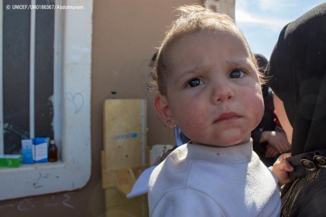 母親に抱えられ、集合型シェルターの外で待つ子ども。(2018年3月17日撮影) (C) UNICEF_UN0186367_Abdulmunem