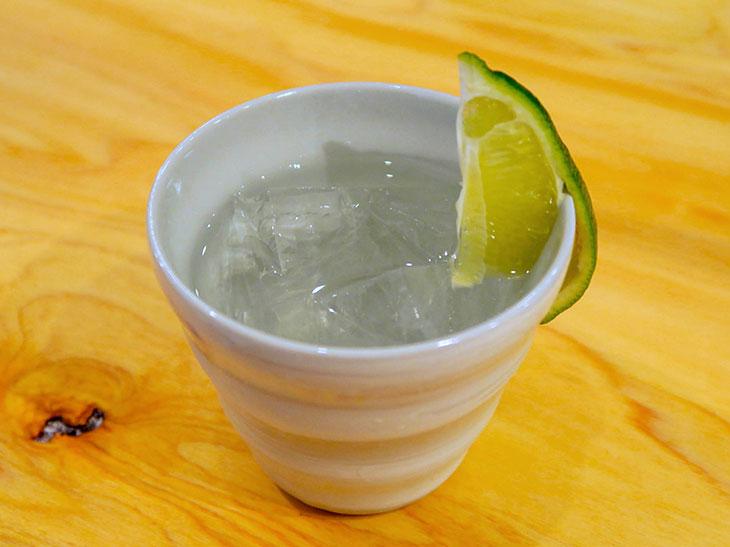 刺し身に合わせるなら○魚特製の「○魚ロック」(500円)。日本酒をロックで飲むオリジナルドリンクで、ライムを絞ると爽やかな味わいに変化する