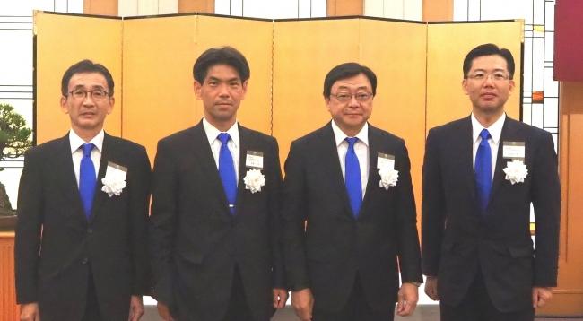 青色発光材料にちなんだブルーのネクタイで 左から 受賞者の松浦正英、舟橋正和、当社代表取締役社長 木藤俊一、福岡賢一