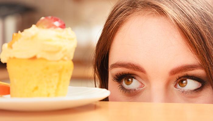 机の上のケーキを見つめる女性