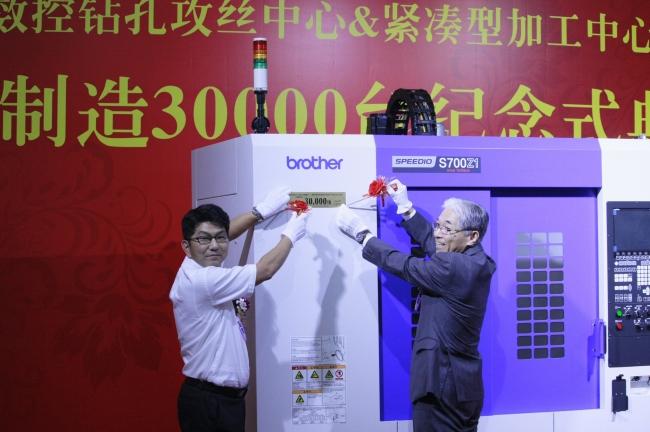 西安工場での式典で生産3万台目記念銘板を取り付ける川那辺専務(右)