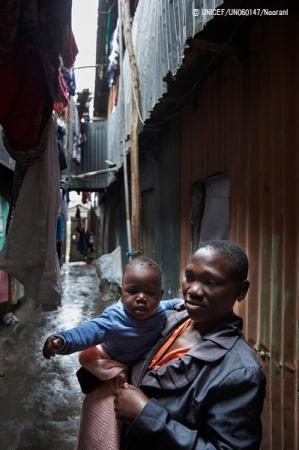 ケニア・ナイロビで、建物の合間の路地に立つ子どもを抱えた母親。(2016年9月撮影) (C) UNICEF_UN060147_Noorani