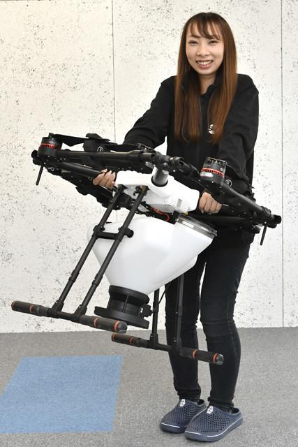 スカイリンクの辣腕営業パーソン、酒井美佑さん。MG-1は折り畳め、女性でも軽々持ち運ぶことができる。農薬散布には産業用マルチローターオペレーター技能認定証が必要