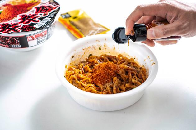 (3)追い辛味! さらにシビ辛カップ麺の限界を目指すため、花椒パウダーとラー油もガッツリ投入。この時点で目にも鼻にも刺激がヤバい! それでも行こうぜ、ピリオドの向こうへ!