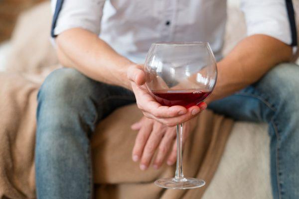 片手にワインを持つ男性