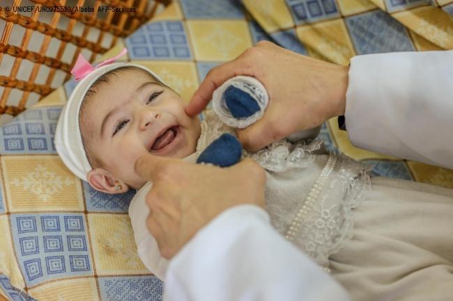 パレスチナ・ガザ地区に設置されたユニセフのECDセンターで、保健員に笑顔を見せる生後10カ月の赤ちゃん。(2019年1月撮影) (C) UNICEF_UN0275530_Albaba AFP-Services