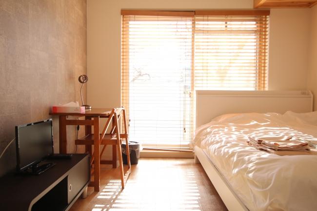 ダブルベッドの個室にはユニットバスとミニキッチン、洗濯機を備え、出張などの長期利用にも対応している。