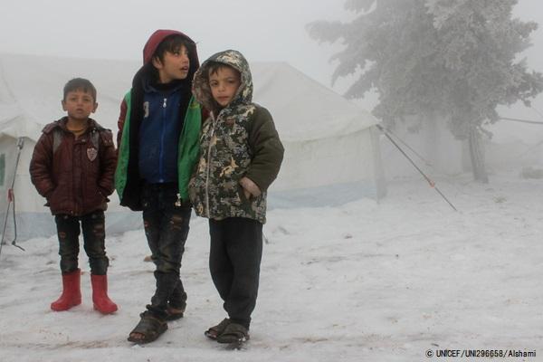 トルコ国境近くの非公式居住区で、厳しい寒さの中テントの外に立つ子どもたち。(2020年2月13日撮影) (C) UNICEF_UNI296658_Alshami