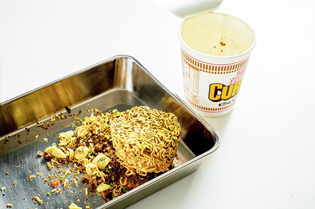 (1)解体! カレーヌードルの容器から麺だけを取り出し、スープとかやくをカップに戻す。麺は軽く潰すと取り出しやすい。準備ができたら溶かしバターでスープとかやくを戻そう