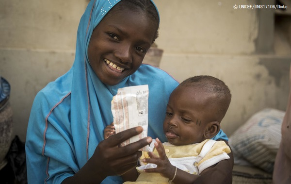 すぐに食べられる栄養治療食(RUTF)を子どもに与える母親。(2020年3月12日撮影) (C) UNICEF_UNI317106_Dicko