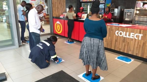 ザンビアの店舗の床に貼られた人との距離を保つためのステッカー(WatrAid Zambia)
